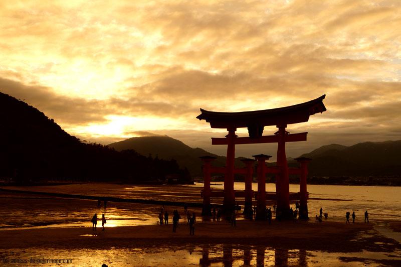 The big red torii of Itsukushima shrine in miyajima at sunset