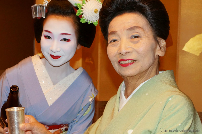 close-up portrait of a maiko (ふく真莉)refilling the pitcher of her older sister at the geisha party