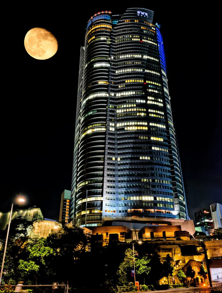 The mori towers in Tokyo at night with the full moon behind it