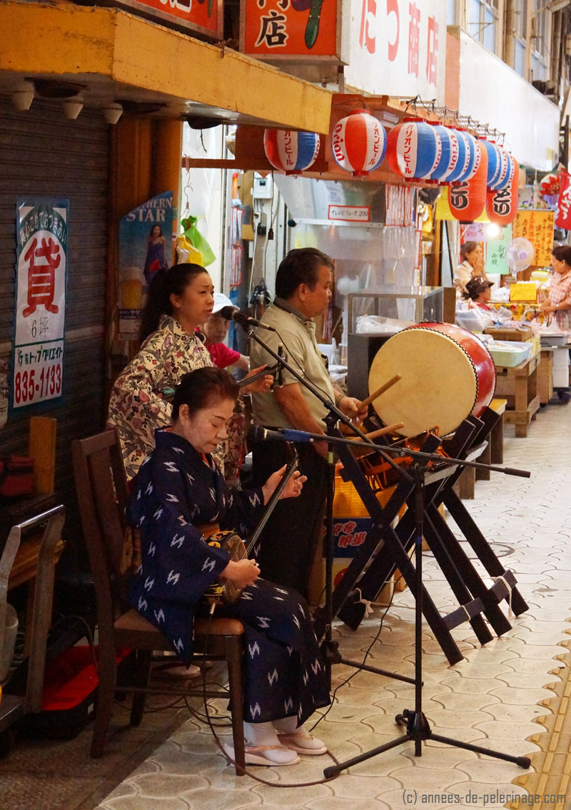 Watching a street band performing traditional music while walking through the shopping district of Naha