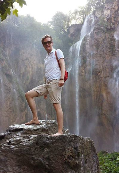 Me on a rock in front of the large waterfall in Plitvice Lakes National Park