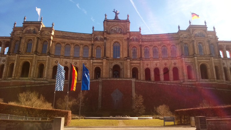 The front view of the Maximilianeum in Munich with three flags