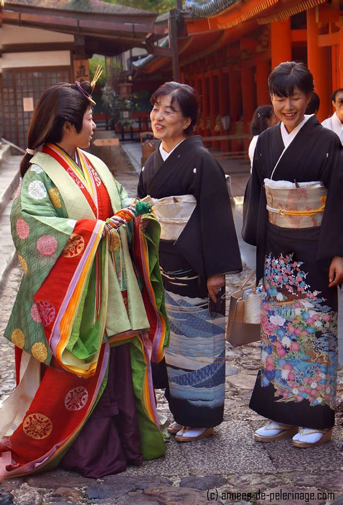 An woman wearing a junihitoe and two japanese women in formal black kimono