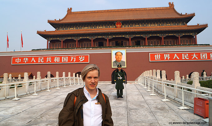 Me standing at the entrance of the Forbidden City in Beijing - a policeman and mao's portrait in the back