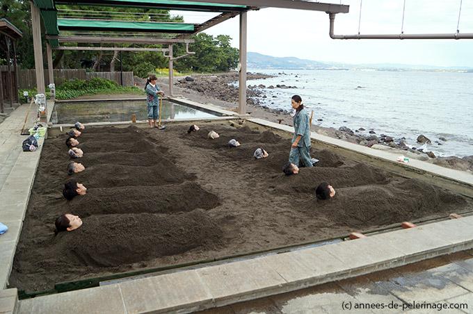 Tourists enjoying a sand bath at the onsen near Beppu Beach