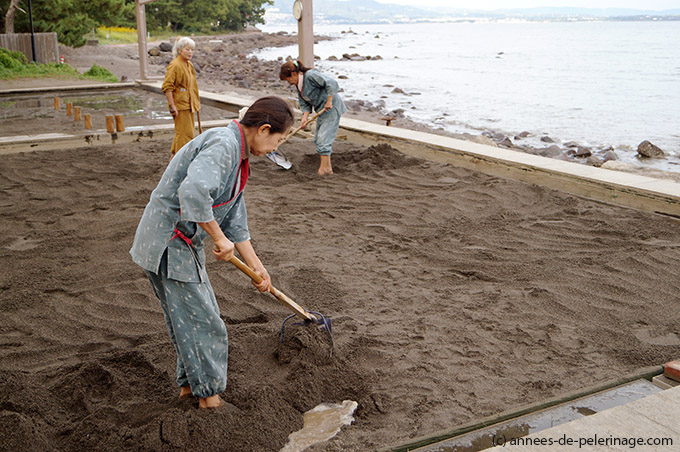 Sand Bath in Beppu - woman preparing the bathing area with a big shovel