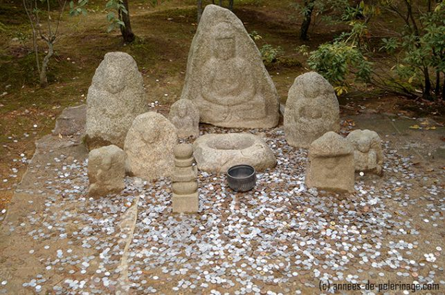Weather worn statues and many coins scattered around the floor - supposedly for luck