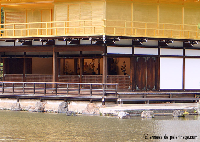the interior of kinkaku-ji and the statues of yoshimitsu on the first floor of the golden temple