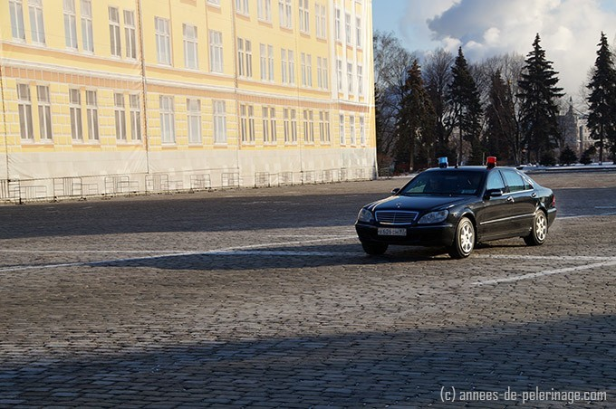 A limo, perhaps with President Putin within, speeding across the cobble stones in Kremlin, Moscow