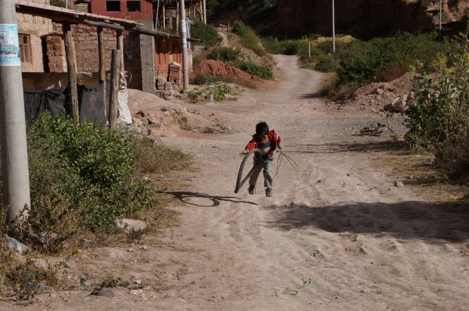 Boy playing with an old tyre in the community of kiachi near the maras salt mines in peru