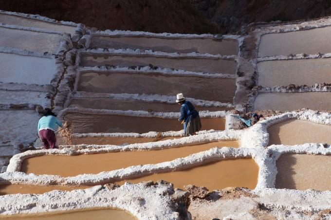 Locals harvesting the pink salts of the maras salineras mines
