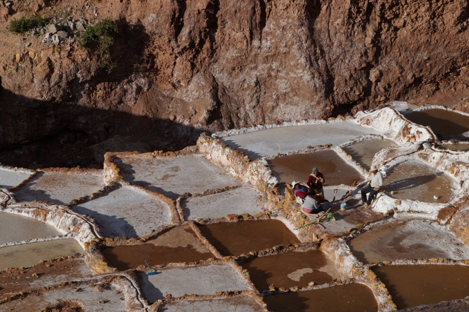 Workers resting on the ridges of the salt mines in Maras, Peru