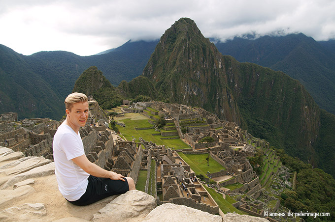 Me sitting on a wall above machu picchu: top destination in my peru itinerary. I packed a lot of light weighted hiking gear for machu Picchu and settled for cotton shirts and short fast drying trekking pants