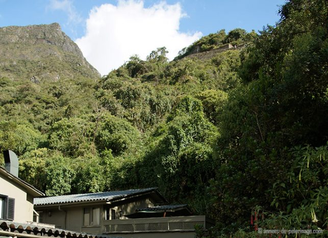 The terrace of the presidential suite of the belmond sanctuary lodge seen from below with parts of machu picchu's ruins in the background