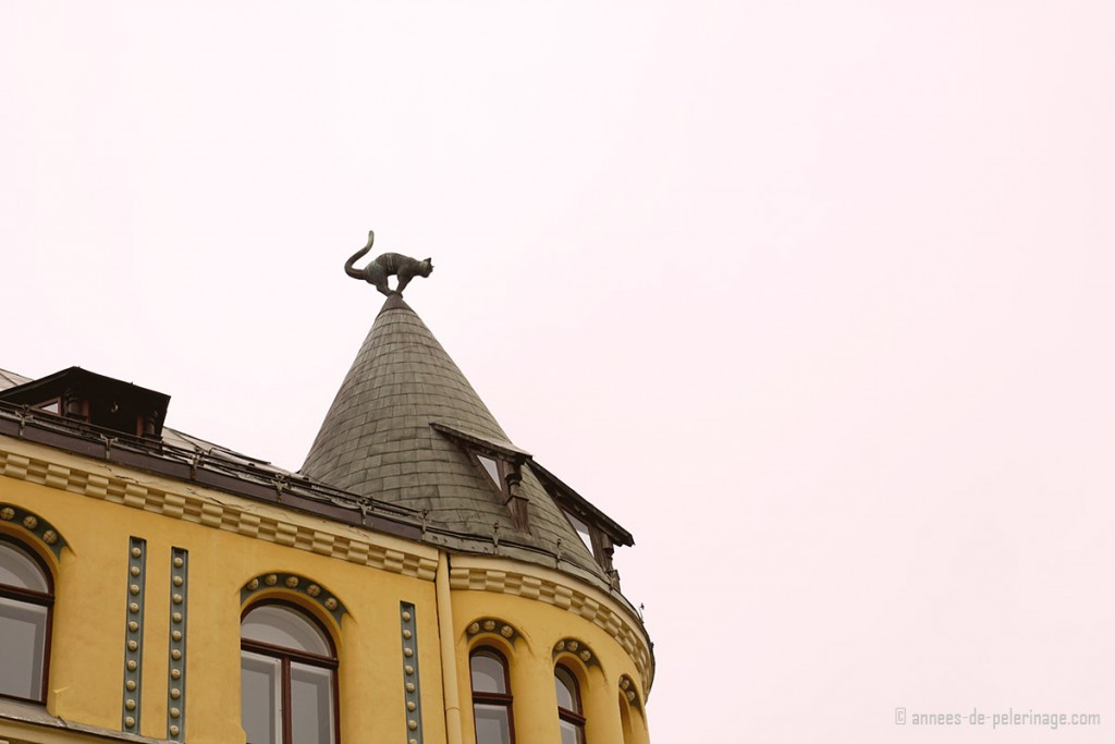 The yellow cat house in riga, with a bronze cat perched on the tip of the tower
