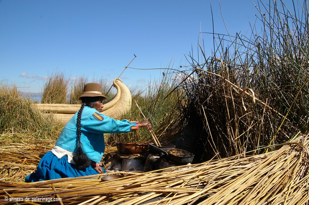 A woman of the uros people cooking traditional food with a reed boat in the background