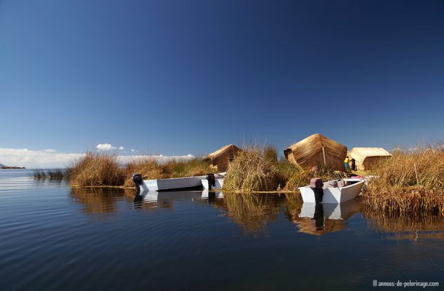Floating island of the Uros people with small motorboats tied to the reeds