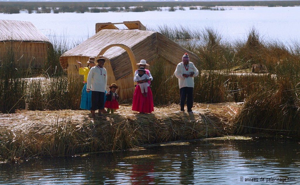The Uros people greeting me from their floating reed island before i enter their domain