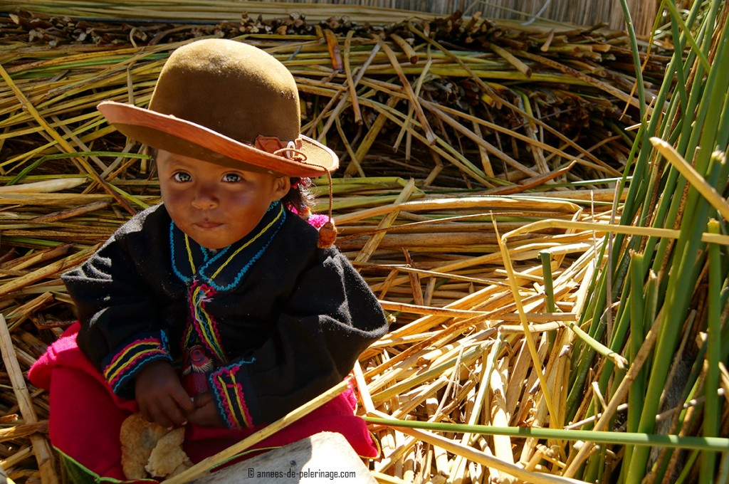 A cute little girl of the Uros people on Lake Titicaca sitting in the reeds
