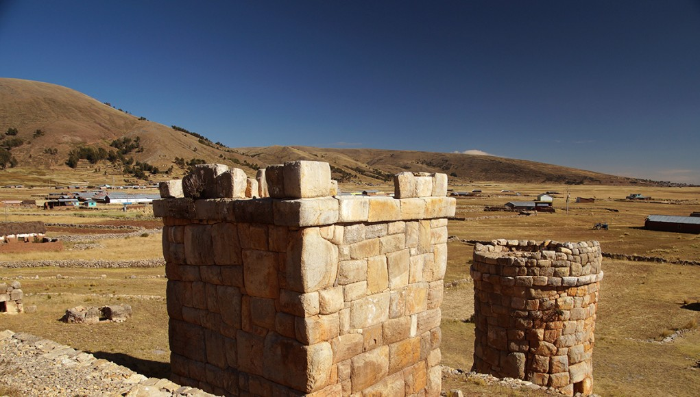 Ancient aymara chullpas near lake titicaca peru, overlooking a small settlement in the ilava district