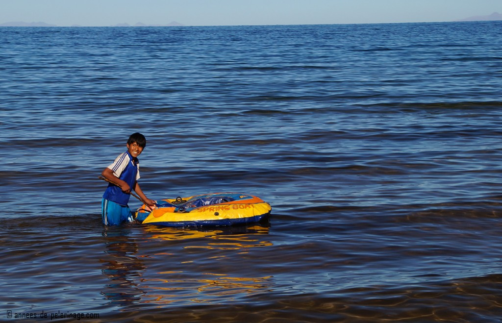 A boy playing in the cold waters of lake Titicaca along the shores of Taquile island