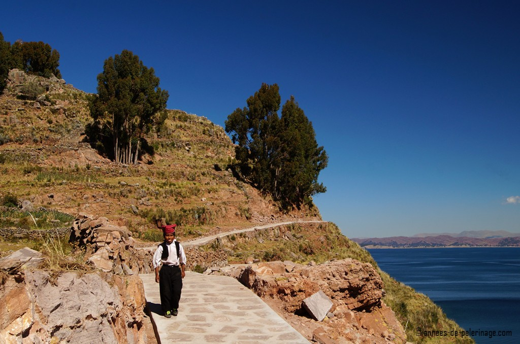 A boy in traditional clothing walking along the pathways of taquile island peru