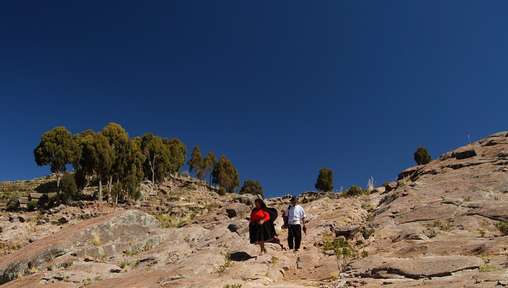 a couple of Taquileños walking down a steep hill on Taquile Island Lake titicaca, peru