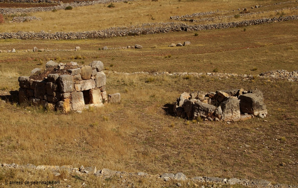 the crumbling ruins of two smaller chullpas near lake titicaca peru