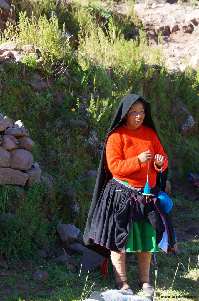 A young girl on taquile island in traditional clothings yarning alpaka yarn