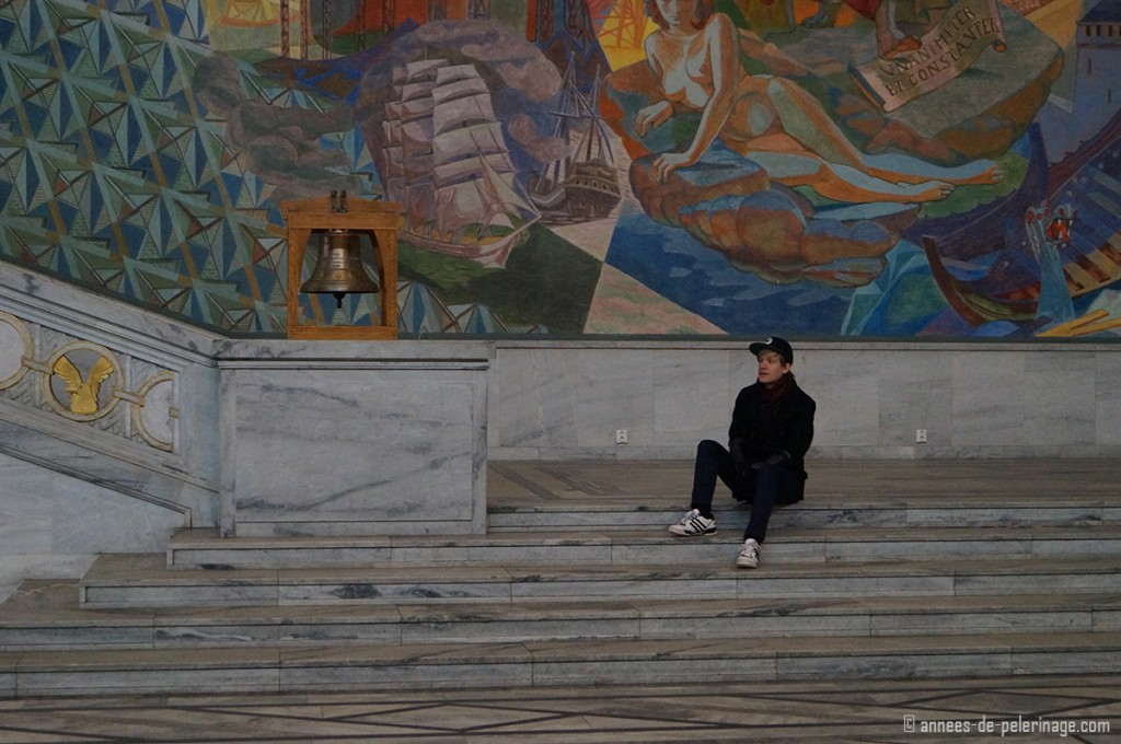 Me sitting inside the city hall in oslo on some raised stairs with a very colorful mural in the background