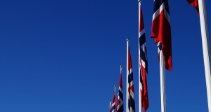 Norwegian flags with only blue sky in the background seen at holmenkollen ski jump
