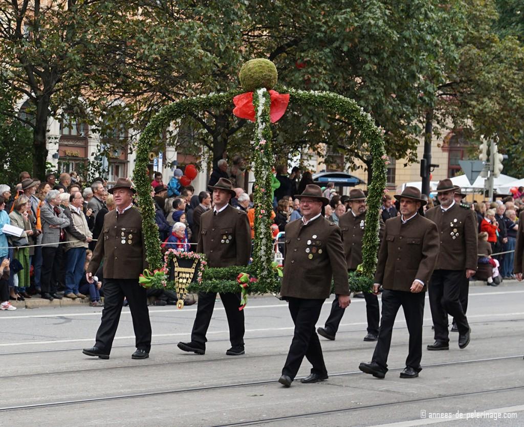 4 men carring a huge flower arch for the oktoberfest parade