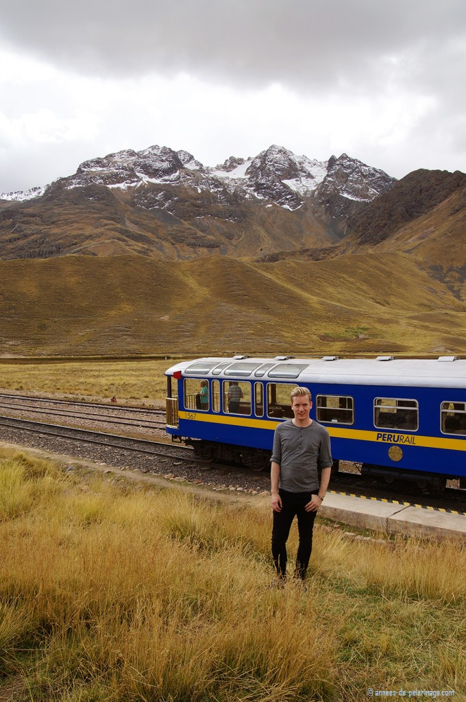 Me standing in front of the Andean Explorer at La Raya Pass with snow covered mountains in the background