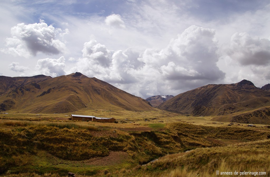 A single cottage standing on the altiplano in peru, with the andes behind it