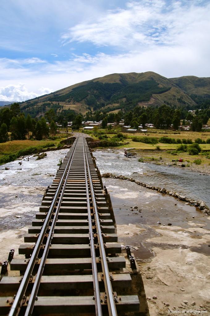 The andean explorer crossing a very narrow bridge over a broad river
