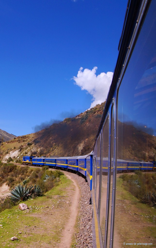 Andean explorer luxury train slowly making its way up to the La Raya Pass with dark steam coming up from the engine