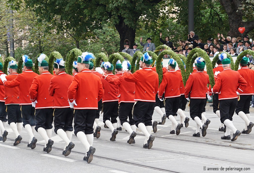 The red livery men of the augustiner bräu marching their multiple greenery arches at the parade