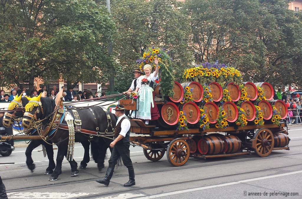 Bräurosl waving to the onlookers sitting on a carriage decorated with sunflowers at the Trachten- und Schützenzug parade in munich