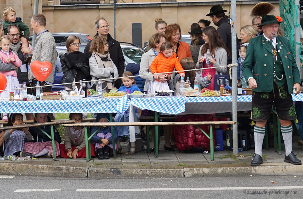 Children watching the costumes parade sitting under a bench while a man with impressive traditional clothes stands by