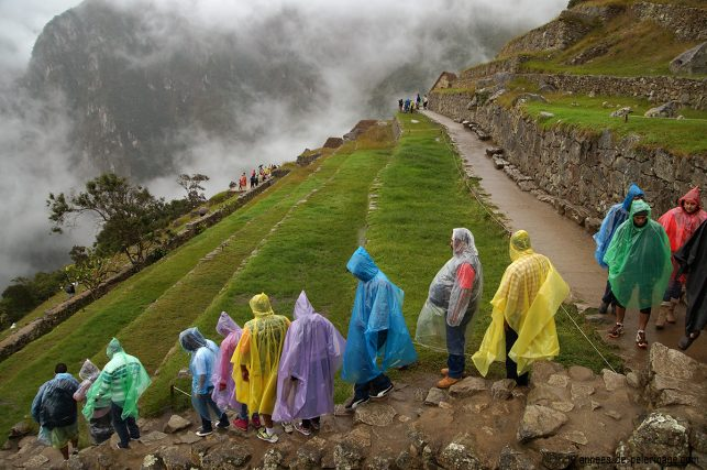 A crowd of tourists wearing rain capes in Machu Picchu. So if you are wondering what to pack for machu picchu & peru in general - bring a poncho