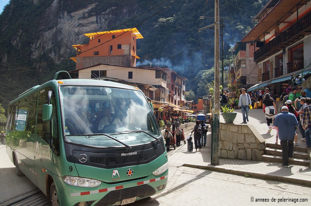 The main road of aguas calientes with a bus to machu picchu in front and thick crowds of tourists behind it