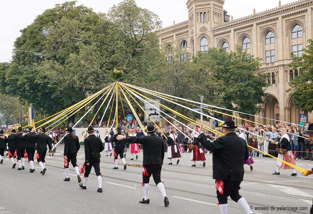 Male and female dancers holding a gigantic dancing pole at the costumes parade in munich
