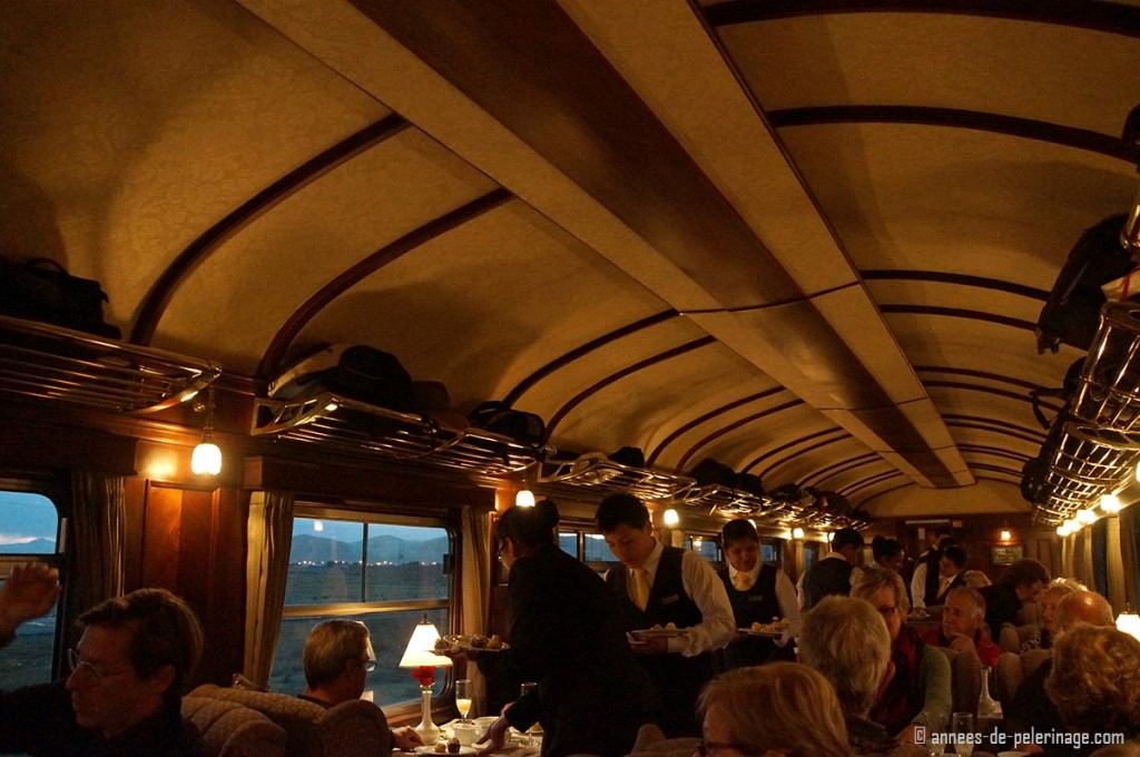 Dinner is being served in the restaurant wagon of the Andean Explorer - outside it is already dark