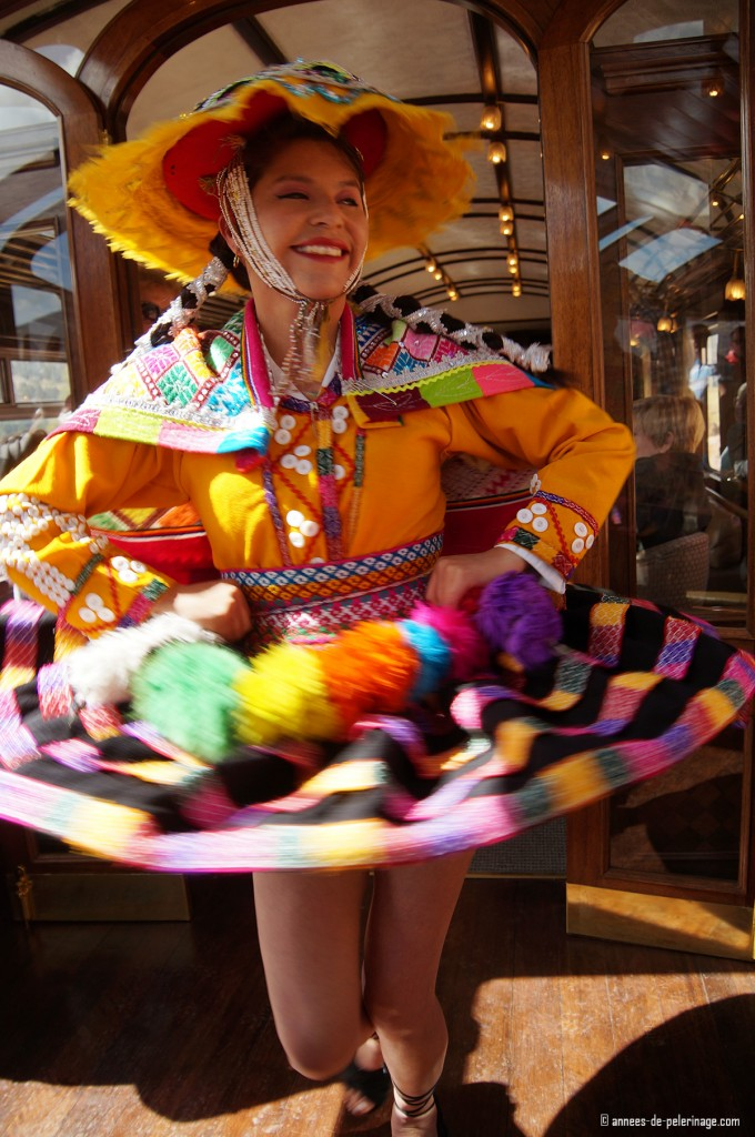 A woman swirling her colorful skirts during the entertainment show onboard the Andean Explorer luxury train