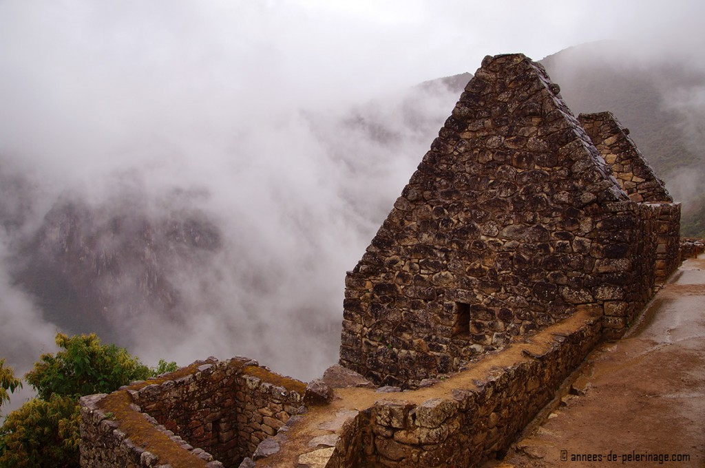A residential house in Machu Picchu with the mountains behind it, partially hidden in fogs