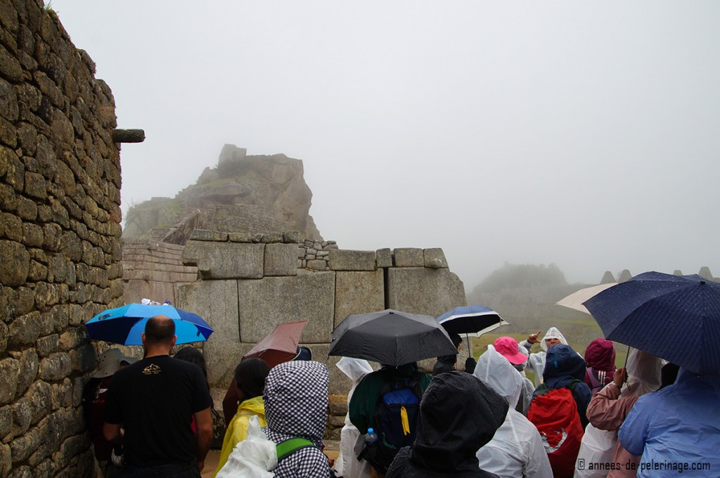 The ruins of machu picchu with a crowd of tourists holding umbrellas to keep dry