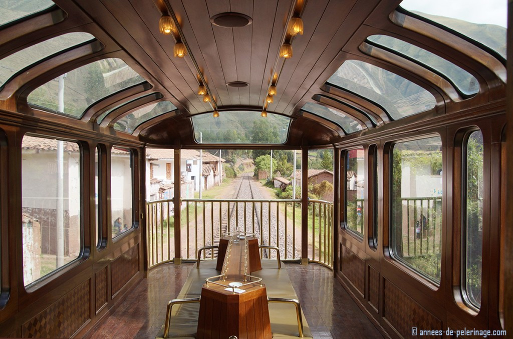 Observation deck of the Andean Explorer luxury train with a village visible through the huge windows