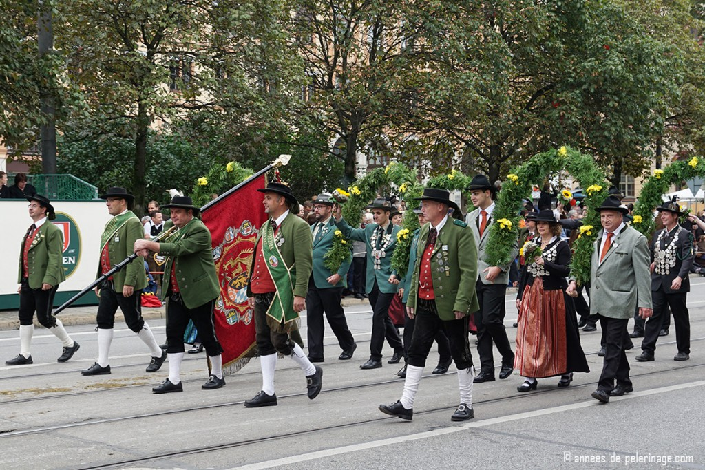 Several master marksmen and markswomen parading under flower arches at Oktoberfest parade