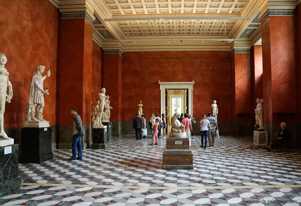 Roman statues in a huge red hall in the basement of the hermitage museum in st. petersburg