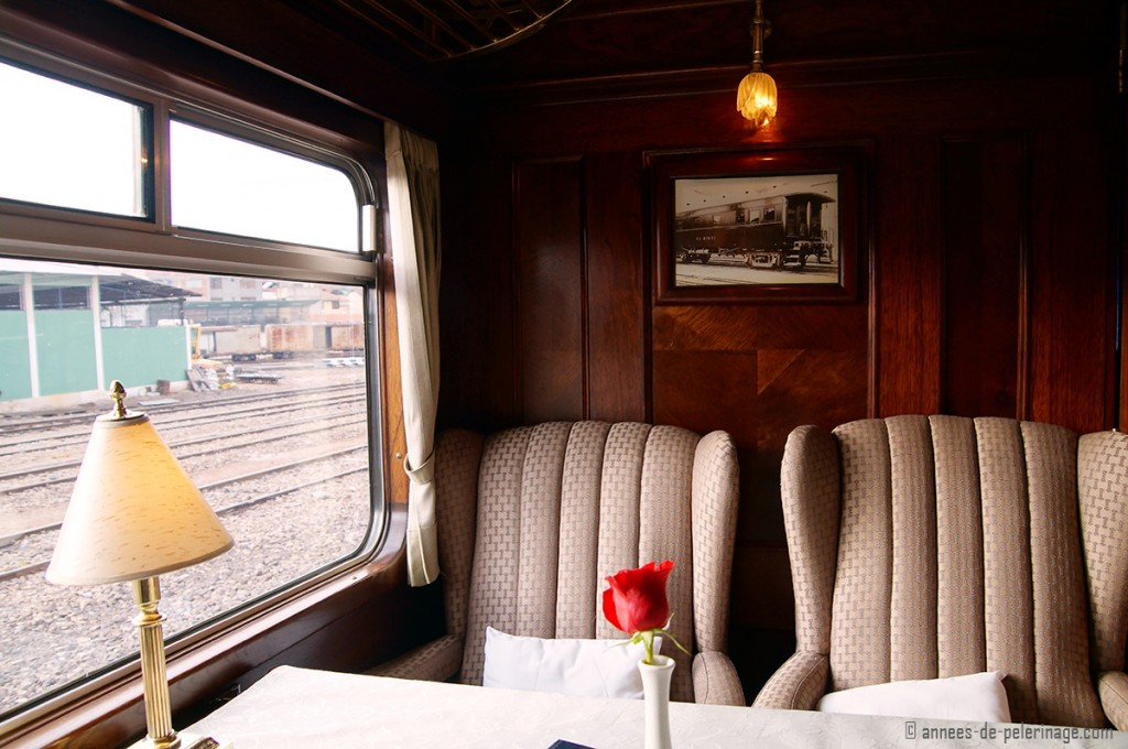 The plush armchair like seats onboard the Andean Explorer Luxury train, with dark wooden panels behind.